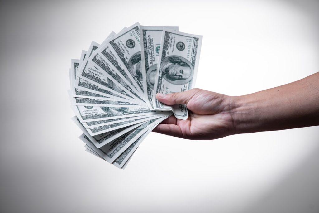 hand holding money package theft refund